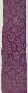 Three panels of chasuble of deep reddish purple fancy satin with large diagonal stylized sprig repeat in cloth weave on satin ground.  Narrow coarse twill selvages with greeen and pale lavender warp stripes.