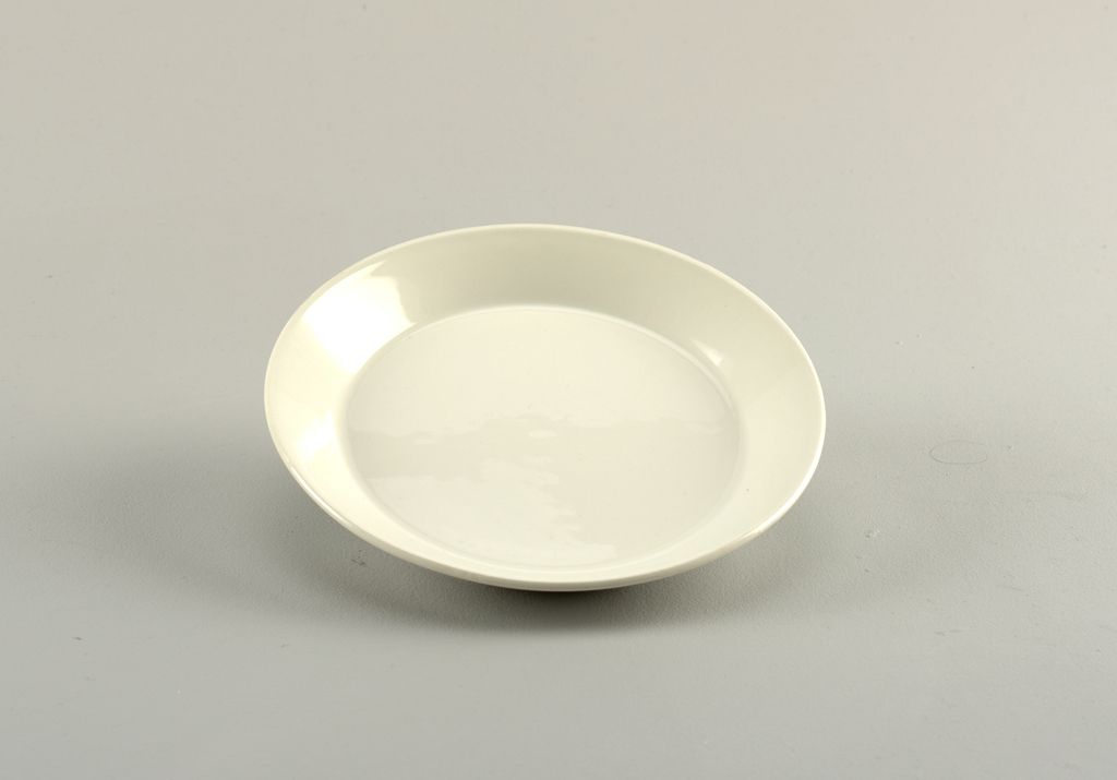 Circular, molded plate. Flat with angled flared rim. Glazed overall with gloss white.