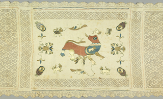 "Rectangular linen table cover with the center panel embroidered in polychrome silks and an ivory drawn work border sewn to all four sides. The embroidery depicts a large ""bicho"" or beast in pink, blue and gold, suckling two small beasts, with a third small beast inside the mother beast; four small beasts are scattered around. In each corner, an owl with a gold face and a pink and blue checkered body, and at each side, a double-headed bird in gold and blue. In the center panel above and below the figures is an additional band of drawn work."