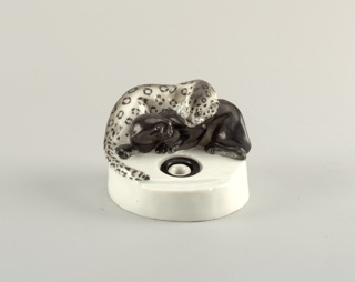 Circular base with inkwell; sitting on top of the base a black panther reclining, with leopard lying on top of it.