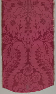 Length of red damask with large scale vertically symmetrical pattern with large leaves and flowers.