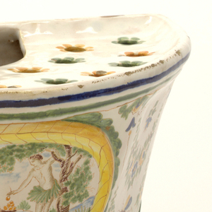 Polychrome with oval medallion and scene of partially nude figures picking apples surrounded by festoons and bees on three foliate scroll feet. Top with alternating blue, yellow sunflower holes.