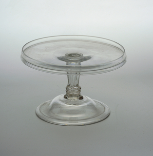 Flat circular tray with up-turned rim; molded, shouldered stem, with slighttwist; domed base with turned-under edge.