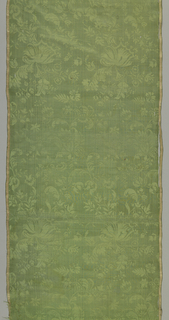 Green damask patterned by a straight repeat of exotic flowers on a very fine curving vine.