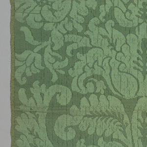 Green damask patterned by a symmetrical arrangement of elaborate flowers, leaves and brackets.