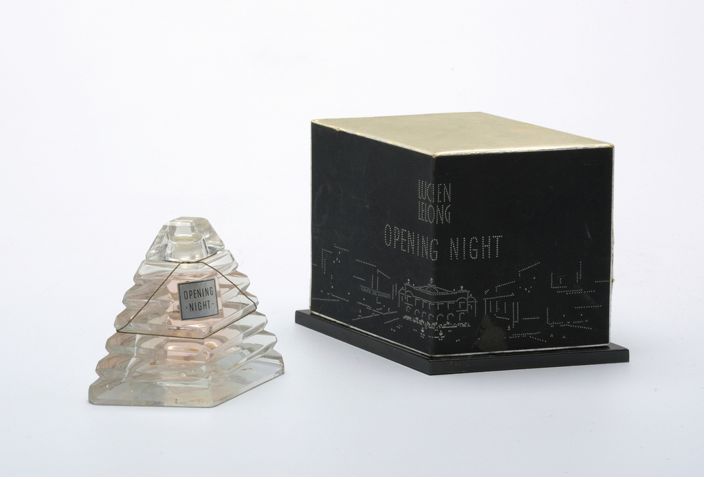 """Bottle and lid in the shape of a ribbed four-sided pyramid, has silvered paper label """"Opening Night;"""" bottle sits on a stepped, diamond-shaped black plastic vase; lid of black paper, inscribed """"Opening Night"""" with stylized Parisian city skyline."""