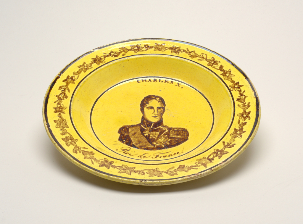 """Circular form with magenta decoration on yellow ground; portrait image of Charles X,  """"Roi de France"""" in center; rim with band of foliate decoration."""
