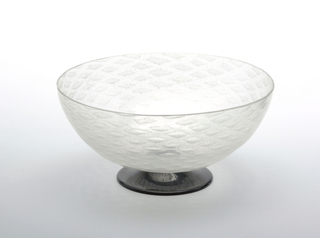 Clear glass textured bowl with a raised and flared foot black foot.