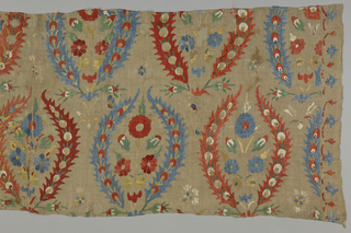 Oblong panel, possibly part of a bed cover, of dark cream linen sheer plain weave embroidered in polychrome silks in red, blue, yellow, white and green, with red and blue predominating. Design consists of one element, a wreath, formed of a long serrated leaf at eath side, open at the top, framing a floral spray.