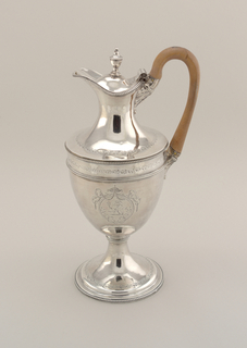 Urn shaped body on stem with stepped, circular foot; urn shaped finial on domed cover extending over lip; body decorated with beading and bright-cut engraving; family arms engraved on both sides; tan wood handle with leaf attachments.