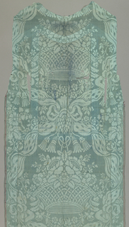 Blue damask with a large scale symmetrical pattern, the vertical center-line is middle of fabric in light blue; large oval frame in the form of a ribbon from the top of which is suspended a basket of flowers from a ribbon.  The ribbon frame is the full width of the fabric, and is repeated one on top of the other.