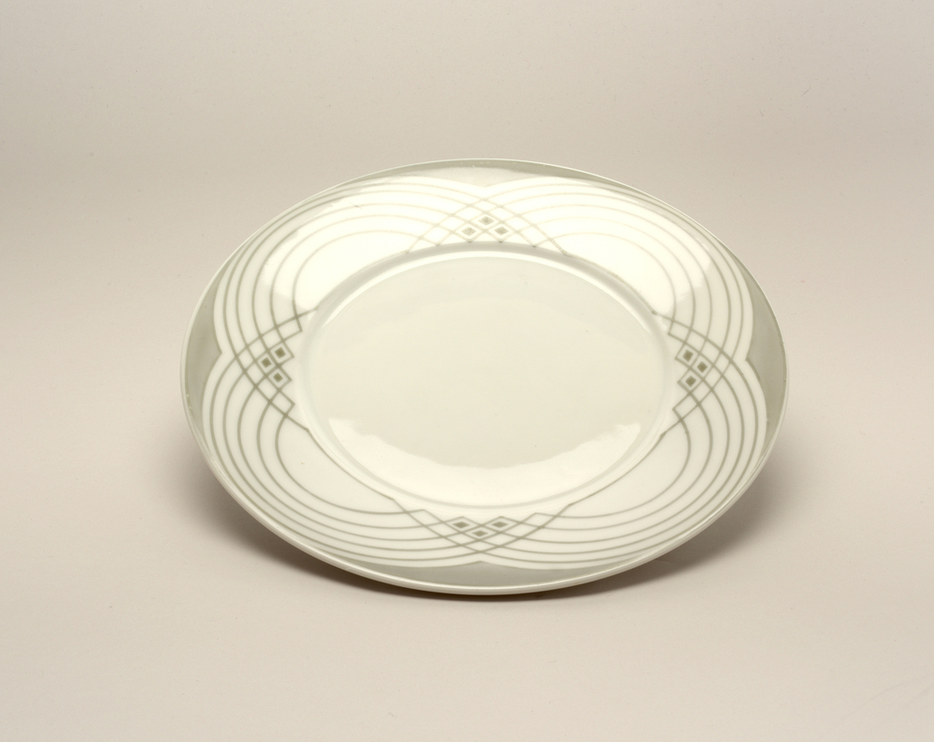 A white porcelain plate with a grey repeating circular pattern around the rim.