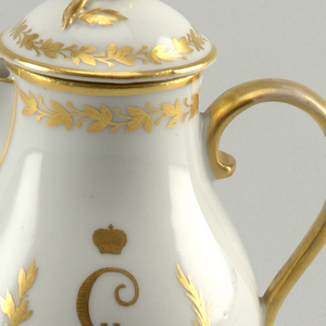 The creamer is a pyriform body on short foot.  Short spout below rim, and strap handle.  Painted on one side the Russian two-headed eagle with St. George in a shield, in black, red and blue.  On other side, monogram of Catherine II, crowned in laurel wreath in gold.  Gold wreath and band around rim, gilt handle.  Cover is fitted with a flower knob and laurel wreath in gold.