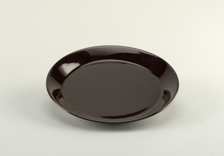 Circular, molded plate. Flat with angled flared rim. Glazed overall with gloss black. Foot ring on underside is unglazed.