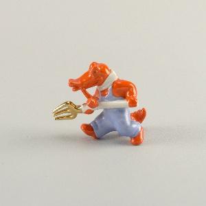 Red/orange crocodile holding pitchfork, striding forward