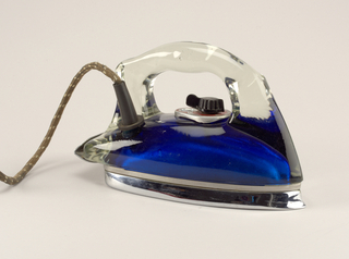 "Broad, oblong wedge-shaped profile comprising one-piece molded transparent glass shroud and handle affixed to white metal soleplate and heel rest. Interior of shroud painted with metalic looking blue emulsion. Fabric-covered power cord emerges from tubular rubber flange at top right side. Black plastic dial on red face-plate inscribed:  ""Off, On, Rayon, Silk, Wool, Cotton, Linen,"" and ""Low, Med, High."""