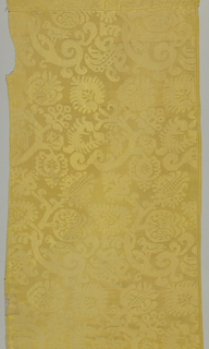 Yellow damask with an allover design of a large scroll pattern. Selvages present.