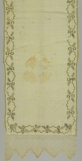 Long narrow shawl of cream colored cotton embroidered at the ends and along the sides in colored silks and paillettes in a leaf and bow-knot design. Scalloped ends of netting woven from the warp ends. Narrow lace edge with narrow band of paillettes at joins.