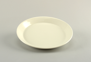 Circular, molded plate. Flat with angled flared rim. Glazed overall with gloss white. Three seggar marks visible on underside.