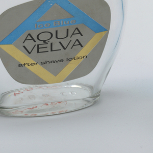"""a) Flat bottle with plastic screw-cap and paper label bearing """"Aqua Velva"""" monogram and fitted legend. b) folding cardboard box bearing """"Aqua Velva"""" monogram and legend. c) folding cardboard box, a smaller version of """"B"""".  Labels and boxes printed in metallic blue, gold, and silver on white with black printing."""