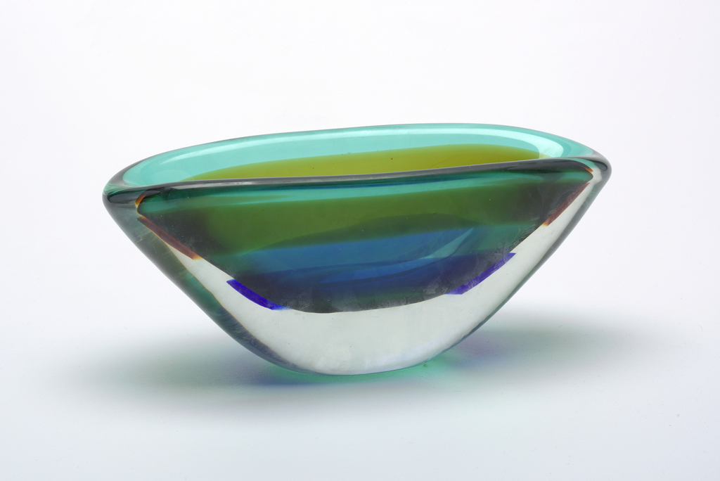 Thick-walled, deep, elliptical bowl; exterior of clear glass, interior of green glass with one encased topaz band and one encased deep blue band; sides gently curve from wide mouth to narrow base.