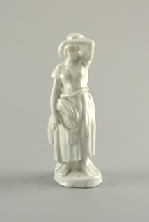 Woman standing, left arm bent over face, holds sickle and sheaf of wheat in right hand, stands on small circular base; unpainted.