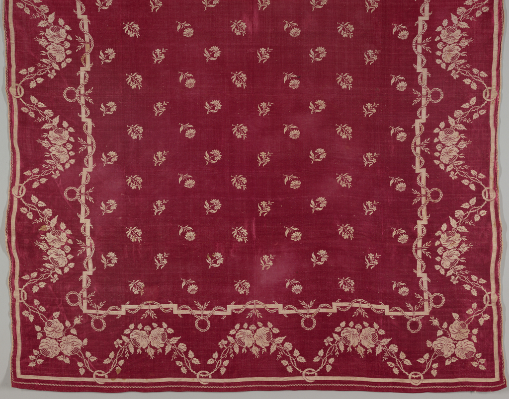 Center field has a straight repeat of four small flowers. Borders have a garland of roses threaded through a ring attached to a bar along the outer edge. Warp ends are hemmed, and weft is selvage to selvage.
