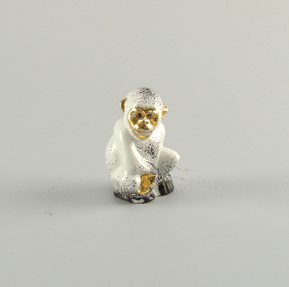 Monkey seated, looking over right shoulder; face, hands, and feet gilded, spotted coat.