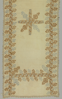 White linen with border embroidered in blue and brown in design of a band of scrolls with diagonally-placed ornaments; in the center an embroidered ornament composed of a cross and four oval motifs. Cover is edged with bobbin lace. Embroidery is in feather stitch.