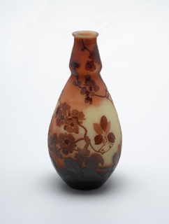 Ovoid body diminishing to neck which flares outward then diminishes again to base of slightly flared lip. Etched decoration of apple blossoms, leaves, and twigs in reddish brown over a shaded citron-to-red-brown background.
