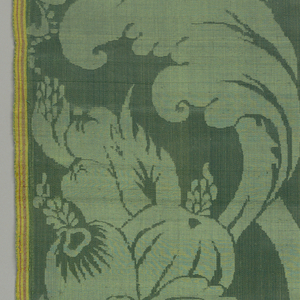 Green damask with a large flower in foliate scrolls with cornucopia-like shapes.
