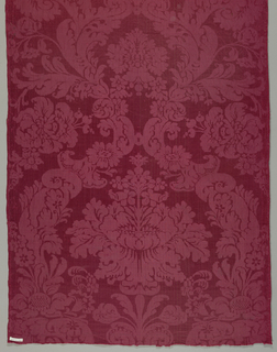 Short length of red damask in a symmetrical arrangement of large flowers and scrolling leaves.