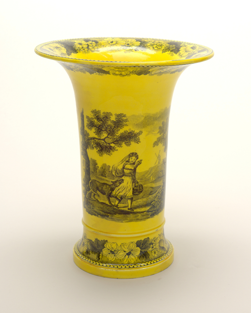 Cylindrical vase with everted rim; black transferware decoration of figure in landscape on a yellow ground; bands of floral decoration at rim and base.