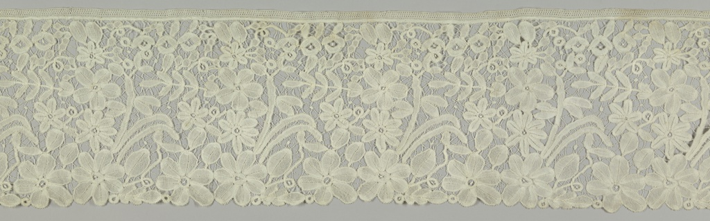 Border with a repeating design of open flowers, leaves and stems all connnected with delicate brides. Brussels technique but Honiton style.