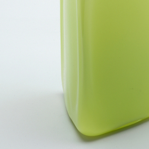 Tall triangular vase, mold blown, with rounded angles and irregular surfaces. Flat base. Body of translucent pale yellow, cased with clear glass. Applied lip thread of blue-green opaque glass.