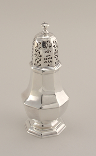 Small George I caster with lid. Octagonal, pear-shaped, baluster form on molded foot. Panels of domed, octagonal cover pierced with alternate scrolls and stylized urns and bouquets; each cover with baluster finial; fitted with bezel closure.