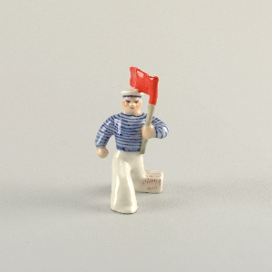 Man wearing cap, striped shirt, striding forward with right leg, holding red banner.