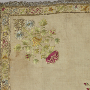 Oblong cover of cream-colored linen embroidred in colored silks and gold thread. Trimmed with a narrow silver lace edge. Corner designs of conventionalized flower sprays with rose or carnation as main flower. Center design of four similar flower sprays springing in cruciform arrangement from center, where a bird with spread wings and crest is seen in profile. If peacock, possibly a symbol of immortality. Border of conventionalized vine, small flowers and strawberries. Pattern arrangement and type of flowers suggest piece was made for liturgical use.