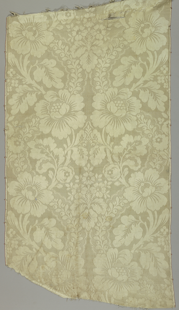 White damask with vertically symmetrical pattern of peonies on a vine crossed by a lace-like ribbon.