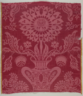 Red damask with a symmetrical arrangement of a large flower coming from a vase.