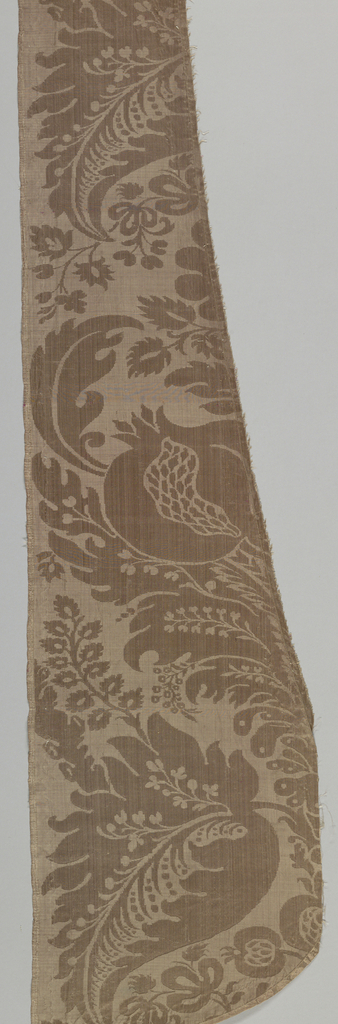 Fragments of a chasuble made from tan and blue damask with a baroque-style pattern.