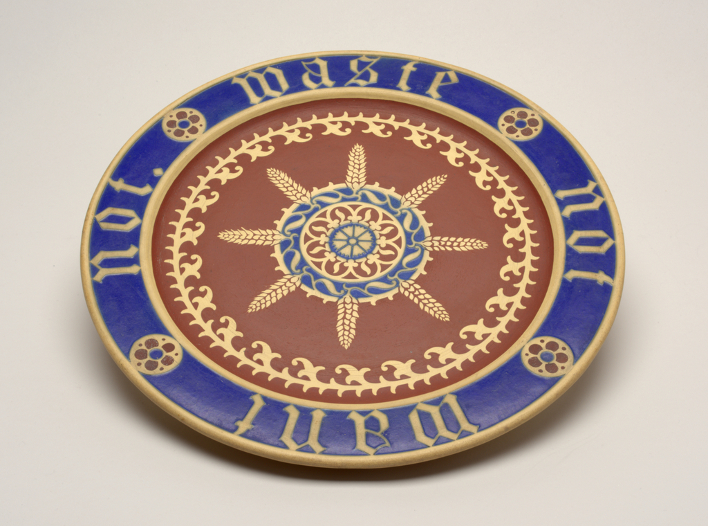 "Circular, with blue border inscribed ""Waste Not Want Not,"" in the center a rosette with ears of wheat and a stylized leaf border."
