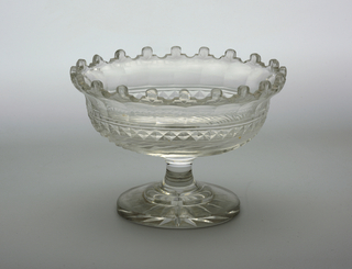 Oval bowl with flared lip and crenellated edge, the sides cut with a band of wide flutes, a band of diamonds below, a band of swirling blazes at the bottom; tall stem, flat circular stepped base cut with star on bottom side.