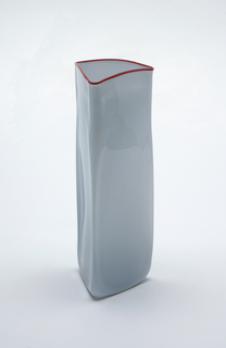 Tall triangular vase, mold blown, with rounded angles and irregular surfaces. Flat base. Body of pale grey translucent glass, cased with clear. Applied lip thread in deep red/brown opaque glass.