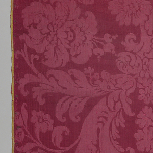 Short length of red damask in a symmetrical arrangement of large and small blossoms and scrolling leaves.