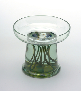 "Pale green, shallow bowl on wide tapered pedestal base with occlusions of white flowers with yellow and white centers and dark green stems and dark blue leaves ""floating"" in solid glass. Ground pontil."