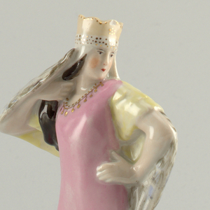 Woman wearing crown, pink dress, large feathered wings and tail; she stands with left hand on hip and right at shoulder; circular base, her head turns to left.