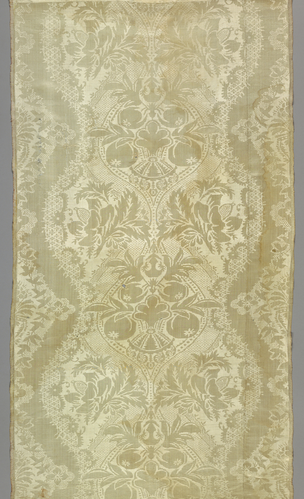 Pieced white damask with a symmetrical vertical ogival repeat with fruits, flowers, and decorative filling patterns. Selvages have three red stripes.