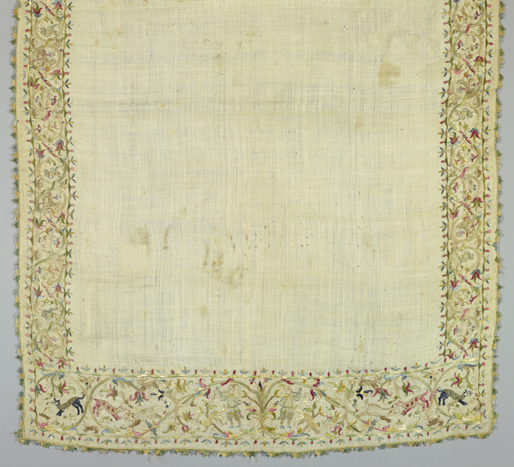 Oblong table cover, cream-colored linen; border embroidered in polychrome silks, light shades. Edged in narrow silk fringe. Design consists of symmetrically curving vines with figures of hunters, hounds, boars, birds and stags. Stitches are satin, darning and running.