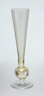 Slightly gold finish on clear glass, fluted glas sits atop of ball and disk foot.